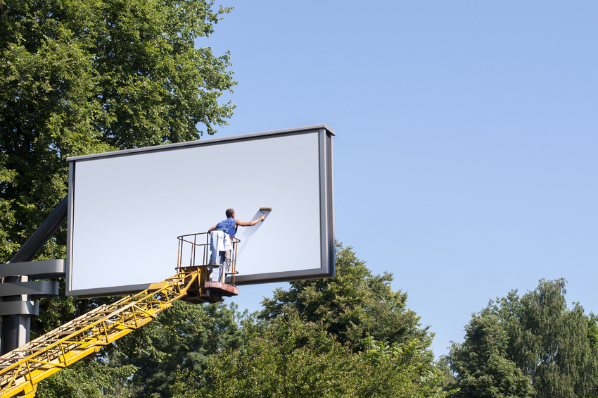 Man putting a new, blank poster to a billboard
